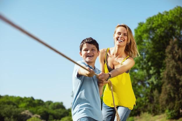 Outdoor activiteiten. waakzame liefhebbende moeder die haar zoon helpt terwijl hij met zijn zus aan een touw trekt
