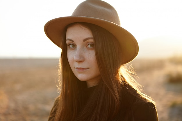 Outdoor close-up portret van tedere jonge romantische vrouw met magnetische ogen, het dragen van hoed, kijken met rust en kleine glimlach, wandelen in het veld, zichzelf in harmonie voelen met de natuur