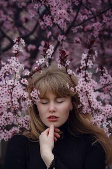 Outdoor fashion foto van een mooie jonge dame in een roze kersenbloesemtuin. als een sakura in japan.