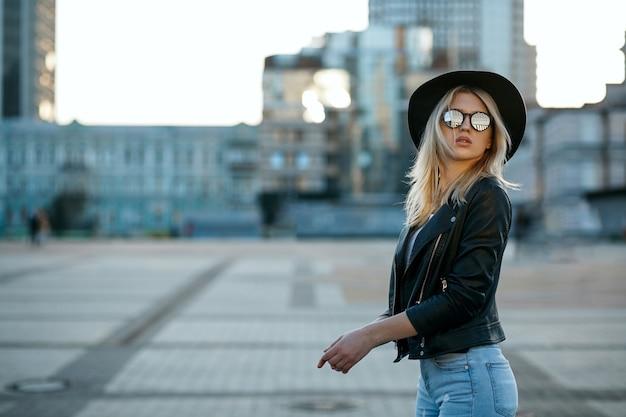 Outdoor fashion portret van een luxe blond meisje met hoed en spiegelglazen. ruimte voor tekst