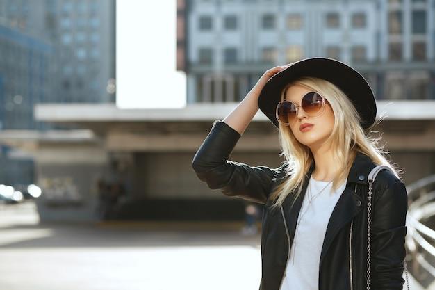 Outdoor fashion portret van een romantisch blond meisje met hoed en vintage zonnebril. ruimte voor tekst