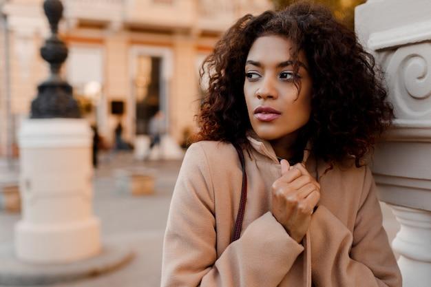 Outdoor fashion portret van glamour sensuele jonge stijlvolle zwarte dame trendy herfst outfit dragen, grijs fluwelen trui en beige wollen jas.