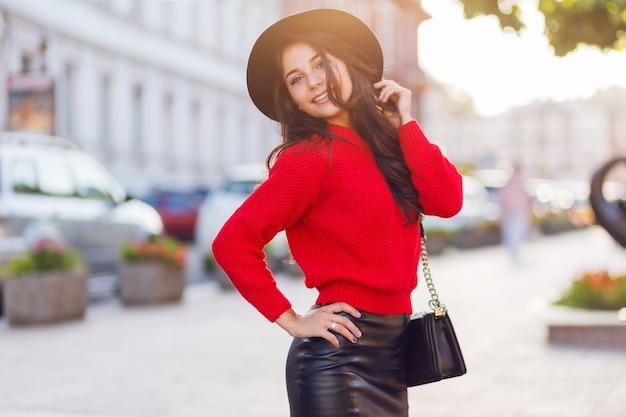 Outdoor fashion street style beeld van verleidelijke brunette vrouw in herfst casual outfit wandelen in zonnige stad. rode gebreide pullover, zwarte trendy muts, leren rok.