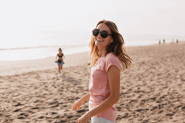 Outdoor foto van gelukkig jong vrouwelijk model in zomer t-shirt staande tegen blauwe lucht en zandstrand vrouw plezier uit op een zomerse dag