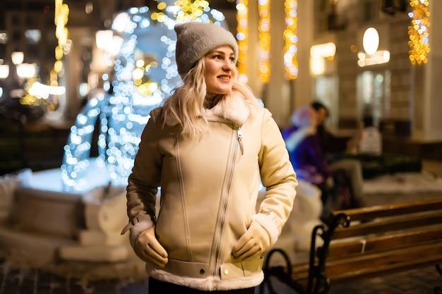 Outdoor foto van jong mooi gelukkig lachend meisje met sterretjes, poseren in straat. feestelijke kerstmarkt op de achtergrond. model met stijlvolle winterjas, gebreide muts, sjaal.