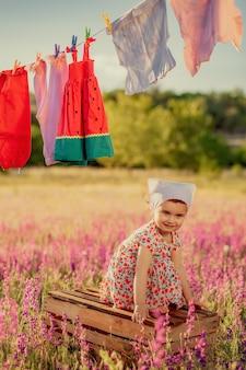 Outdoor fotoshoot van schattig klein meisje in lavendelveld staande op houten kist en plezier