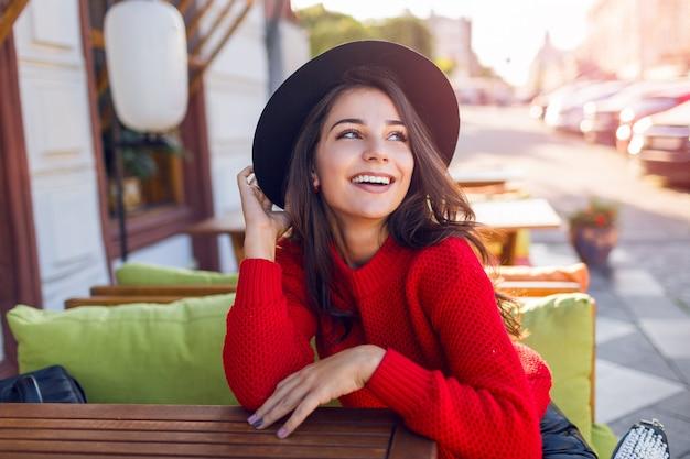 Outdoor herfst mode portret van sierlijke lachende jonge vrouw in gezellige warme gebreide trui. leuke dame zitten in café, koffie drinken