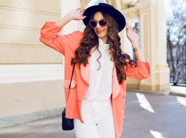 Outdoor hight fashion portret van sexy stijlvolle casual vrouw in zwarte hoed, roze pak, witte blouse poseren op oude straat. lente, herfst zonnige dag. golvend kapsel.