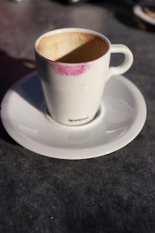 Outdoor koffiemok met rode lippenstift gemarkeerd op de mok