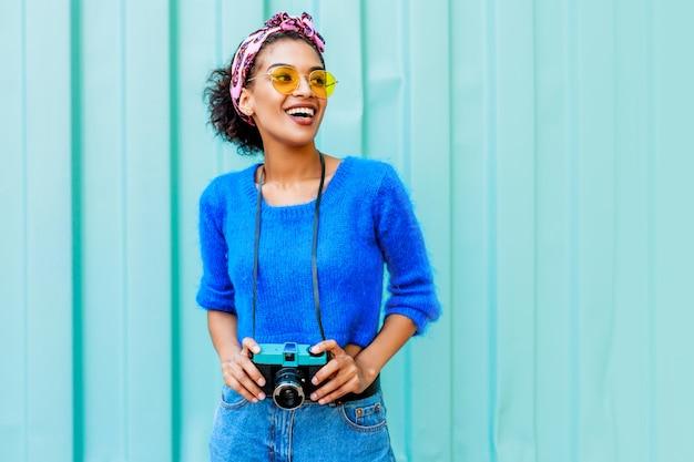 Outdoor lifestyle afbeelding van modieuze zwarte vrouw in heldere wollen trui en kleurrijke hoofdband op haren