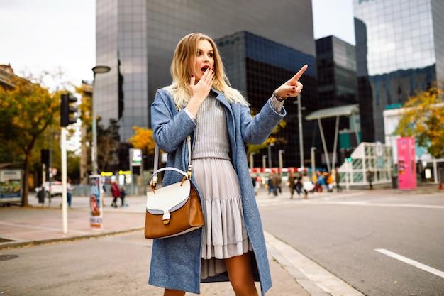 Outdoor lifestyle portret van blonde mooie jonge zakenvrouw, wandelen op gebied van moderne gebouwen, gekleed in een blauwe jas en vrouwelijke grijze jurk, verrast enge emoties, iets door haar vinger laten zien.