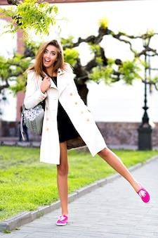 Outdoor lifestyle portret van elegante vrouw wandelen in het centrum van europa, plezier hebben en glimlachen, beige jas en glamour jurk dragen, hipster stemming, vakantie, herfst tijd reizen.