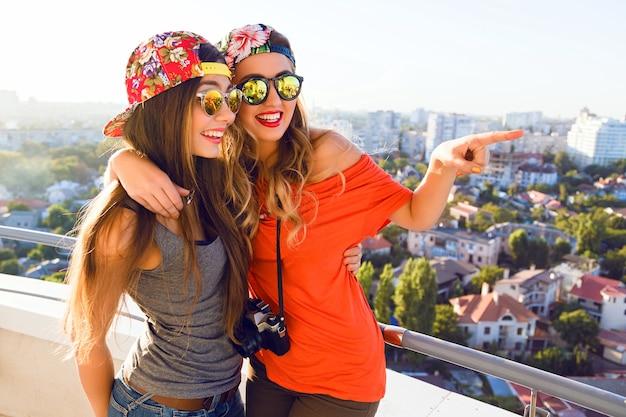 Outdoor lifestyle portret van twee beste duivels zusters meisjes die zich voordeed op het dak