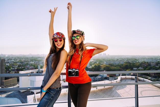 Outdoor lifestyle portret van twee mooie stijlvolle beste vrienden poseren op het dak met een prachtig uitzicht op de stad, hun handen in de lucht, schreeuwend lachen, gek worden en genieten van hun vrijheid