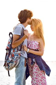 Outdoor lifestyle portret van verbazingwekkende mooie jonge paar verliefd poseren op het strand. stijlvolle man en vrouw knuffelen en brengen geweldige tijd samen door. gebloemde jurk rugzak en denim.