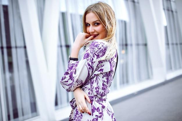 Outdoor lifestyle portret van verlaten lachende blonde vrouw elegante trendy bloemen jurk dragen en kijken in de camera, lente zomertijd.