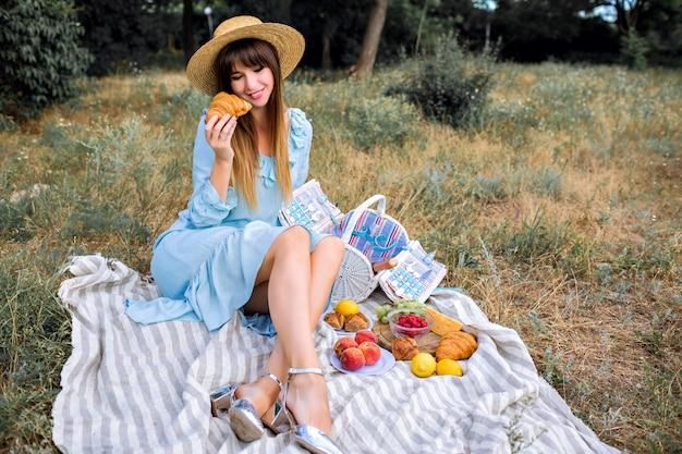Outdoor lifestyle portret van vrij elegante prachtige stijlvolle vrouw, gekleed in blauwe vintage vrouwelijke jurk en strooien hoed