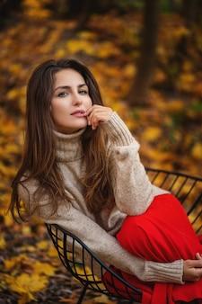 Outdoor mode foto van jonge mooie dame omringd herfstbladeren