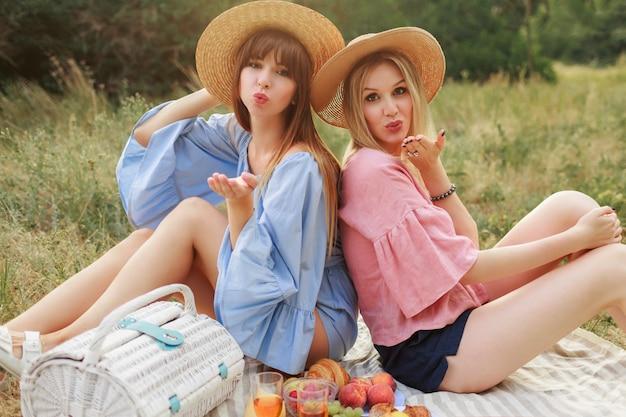 Outdoor mode foto van twee aantrekkelijke vrouwen in strooien hoed en zomerkleren genieten van piknik.
