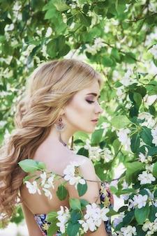 Outdoor mode mooie jonge vrouw omringd door lila bloemen zomer. lila struik in de lentebloesem. portret van een blond meisje