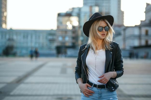 Outdoor mode portret van een glamour meisje met hoed, spiegel bril en stijlvolle outfit. ruimte voor tekst