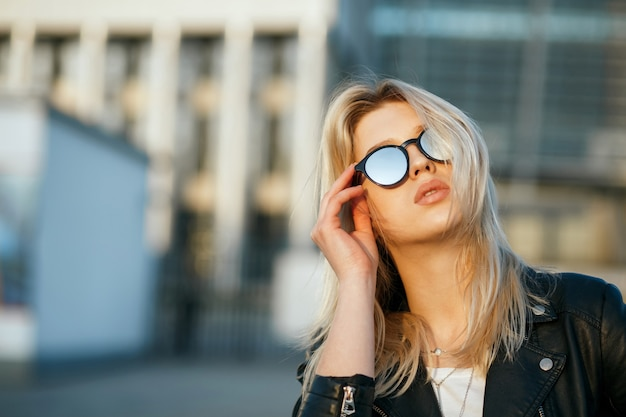 Outdoor mode portret van een modieuze blonde vrouw spiegel zonnebril dragen. ruimte voor tekst