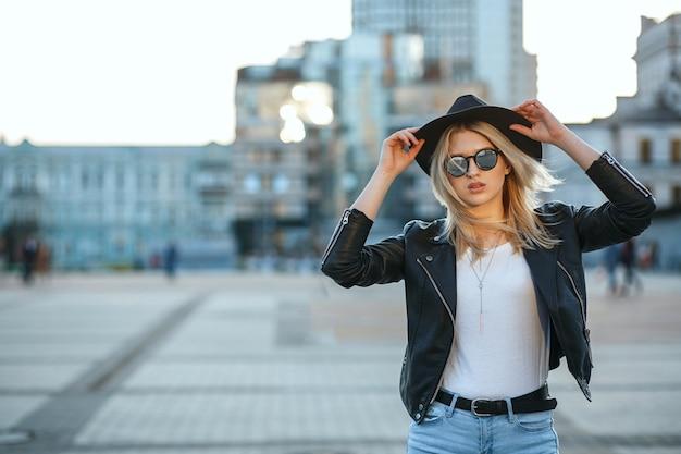 Outdoor mode portret van een mooie blonde vrouw met hoed en spiegel zonnebril. ruimte voor tekst