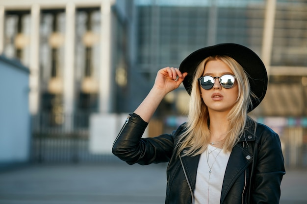 Outdoor mode portret van een prachtige blonde vrouw met hoed en spiegel zonnebril. ruimte voor tekst