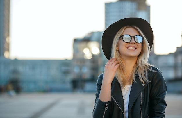 Outdoor mode portret van een vrolijke blonde vrouw met hoed en spiegel zonnebril. ruimte voor tekst