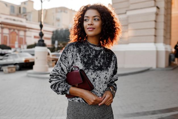 Outdoor mode portret van glamour sensuele jonge stijlvolle zwarte dame trendy herfst outfit, grijs fluwelen trui en luxe portemonnee dragen.