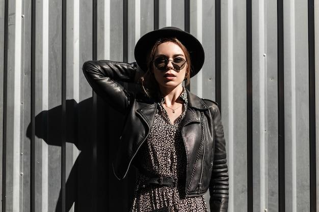 Outdoor mode portret van mooie vrouw met zonnebril in stijlvolle jurk met leren jas en hoed in de buurt van een metalen wand op een zonnige dag