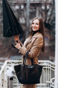 Outdoor mode portret van stijlvolle jonge vrouw met plezier, emotioneel gezicht, lachen, urban city street style, donkere casual broek, witte trui, romige jas en zonnebril dragen. mode concept.