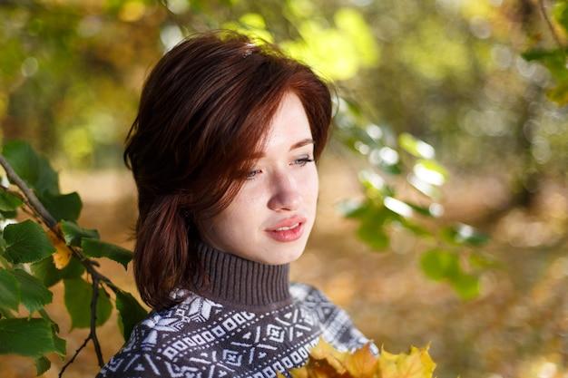 Outdoor portret jonge blanke vrouw in gebreide trui poseren tegen natuur achtergrond beau