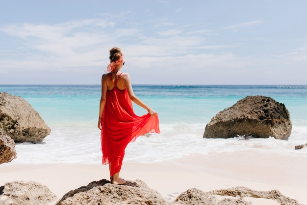 Outdoor portret van achterkant prachtige blanke vrouw genieten van uitzicht op zee in weekend. het schot van gemiddelde lengte van tevreden meisje dat in lange kleding hemel dichtbij oceaan bekijkt.