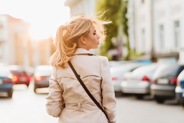 Outdoor portret van achterkant serieuze dame in beige jas op zoek weg staande op straat