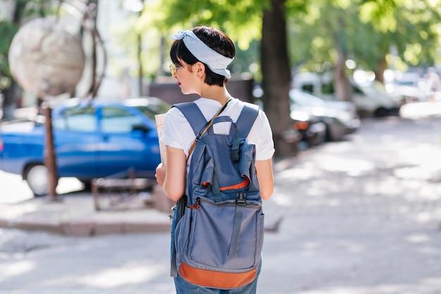 Outdoor portret van achterkant sierlijke vrouwelijke reiziger met kort zwart haar tijd buiten wandelen door auto 's doorbrengen
