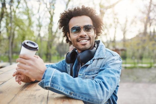 Outdoor portret van charmante stijlvolle donkere man met afro kapsel, trendy bril en denim jas terwijl op straat, leunend op tafel, koffie drinken