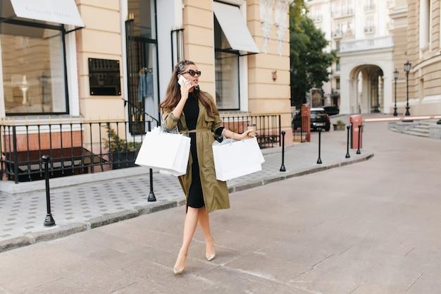 Outdoor portret van drukke elegante vrouw in trendy hoge hak schoenen praten over de telefoon op straat en rondkijken