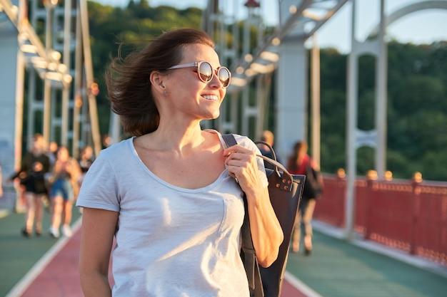Outdoor portret van een gelukkig lachende volwassen vrouw in zonnebril lopen op brug, gouden uur, zomerseizoen