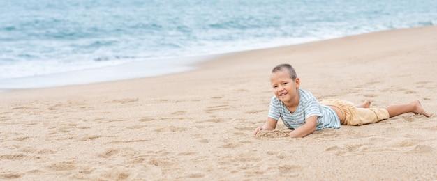 Outdoor portret van een kleine schattige jongen tot op het zandstrand. panorama