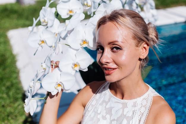 Outdoor portret van een vrouw in een witte trouwjurk, zittend in de buurt van blauwe zwembad met bloemen