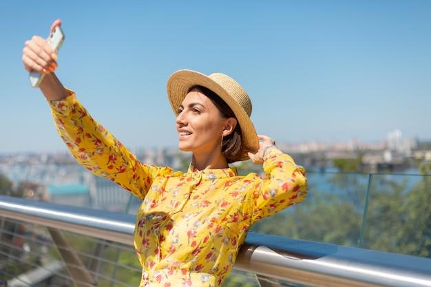 Outdoor portret van een vrouw in gele zomerjurk en hoed nemen selfie op telefoon, staat op de brug met prachtig uitzicht op de stad