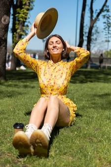 Outdoor portret van een vrouw in gele zomerjurk en hoed zittend op het gras in het park