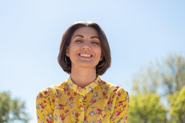 Outdoor portret van een vrouw in gele zomerjurk op zoek naar camera met een enorme glimlach