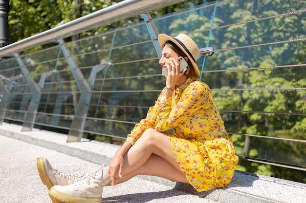 Outdoor portret van een vrouw in gele zomerjurk zittend op de brug bellen, praten op de mobiele telefoon
