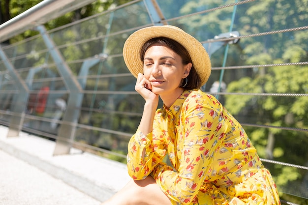 Outdoor portret van een vrouw in gele zomerjurk zittend op de brug met gesloten ogen, gelukkige stemming, genieten van zonnige zomerdagen