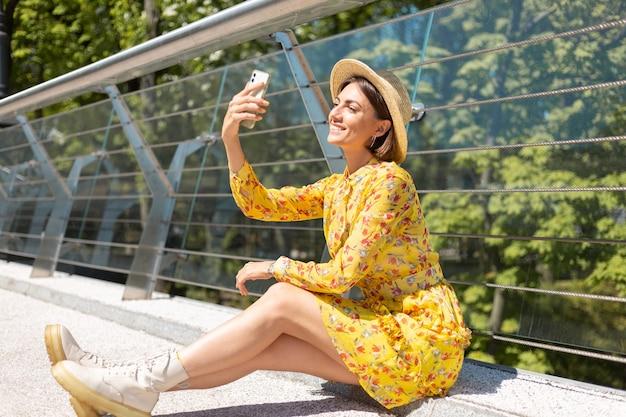 Outdoor portret van een vrouw in gele zomerjurk zittend op de brug selfie te nemen op de mobiele telefoon