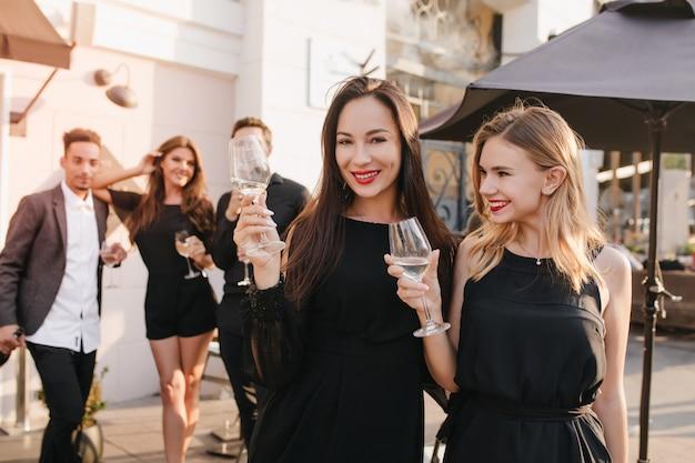 Outdoor portret van enthousiaste brunette vrouwen in zwarte jurken poseren