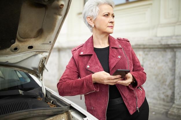 Outdoor portret van ernstige volwassen zakenvrouw in stijlvolle kleding poseren op haar kapotte auto met open kap, mobiele telefoon te houden