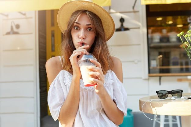 Outdoor portret van gelukkig mooie jonge vrouw met gesloten ogen draagt stijlvolle hoed, voelt zich ontspannen en afhaalmaaltijden koffie drinken in de stad in de zomer